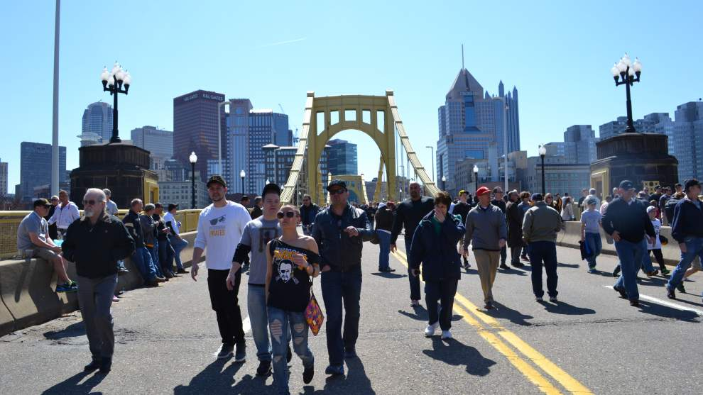 Fans walk over Clemente Bridge